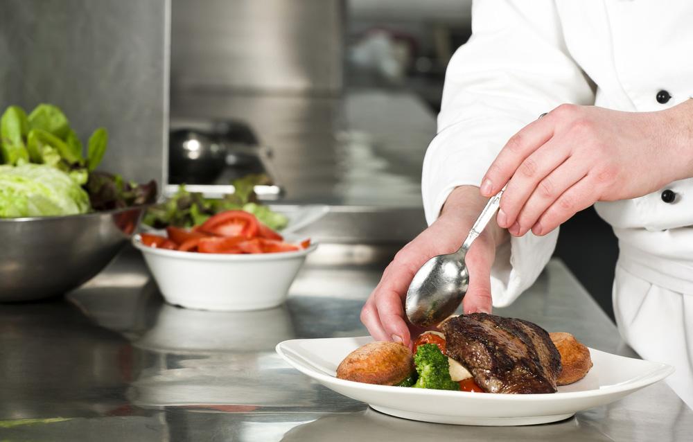 Koch beim anrichten  Front Cooking ist Unterhaltung pur - 360° Catering