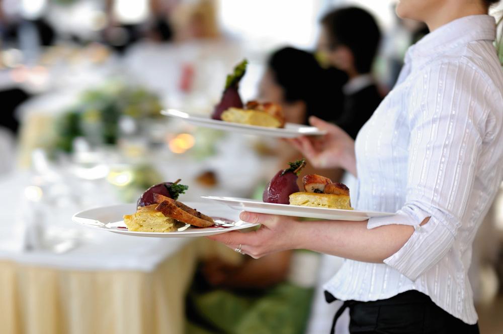 Bedienung mit angerichteten Tellern beim Servieren